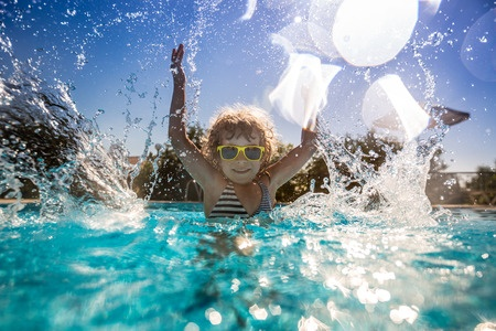 39362972 - happy child playing in swimming pool. summer vacation concept